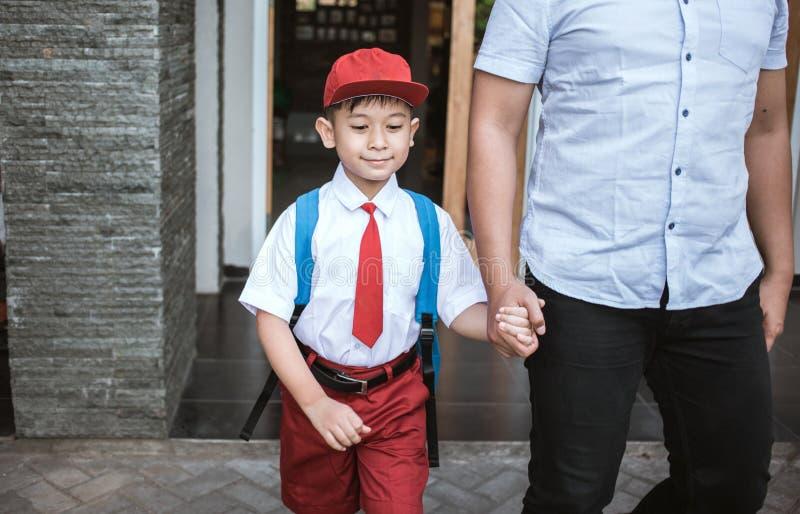 El padre toma a su hijo elemental del estudiante que va a enseñar imagen de archivo