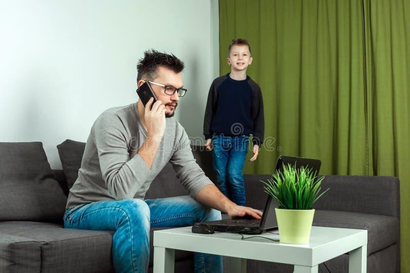 El padre trabaja en un ordenador portátil en casa, su hijo lo molesta Hombre de negocios que trabaja de hogar y que se ocupa a un fotografía de archivo
