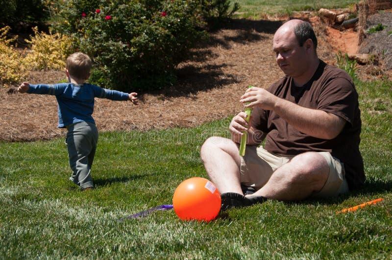 El padre utiliza una máquina de la burbuja para producir las burbujas que su hijo joven funciona con después imágenes de archivo libres de regalías
