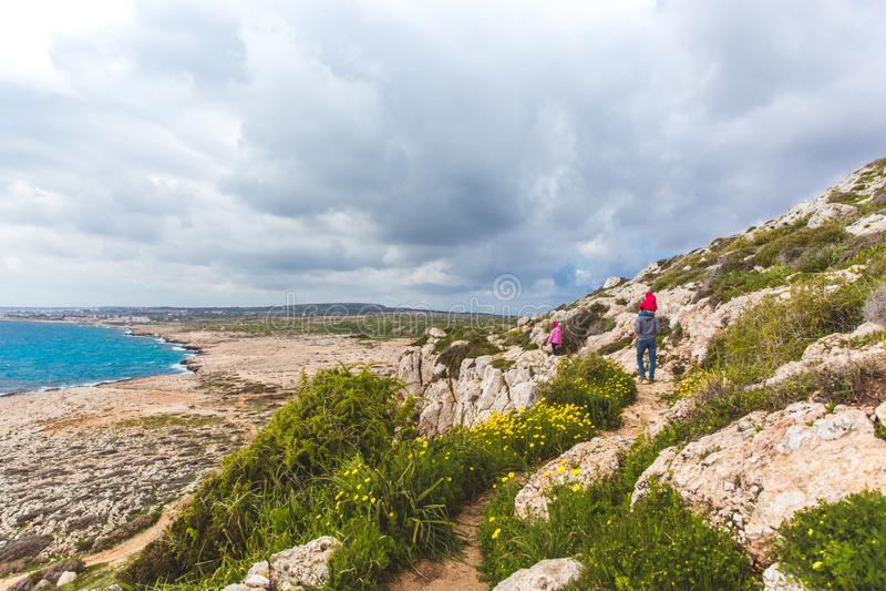 El padre y dos hijas caminan a lo largo de la trayectoria a lo largo del mar Valle hermoso por el mar Paisaje marino en Chipre Ay fotos de archivo libres de regalías