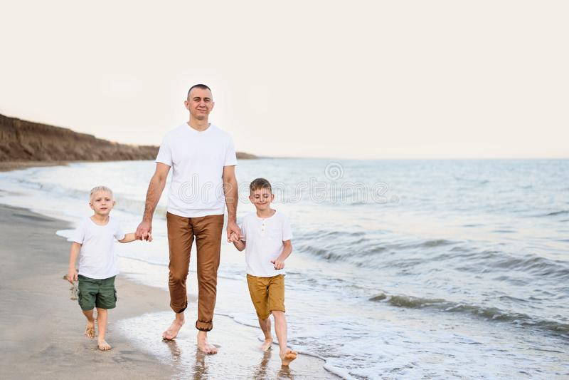 El padre y dos hijos caminan a lo largo de la costa Disfrutar de vacaciones imágenes de archivo libres de regalías