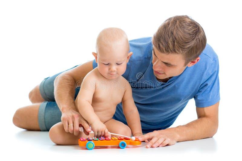 El padre y el bebé se divierten con los juguetes musicales imágenes de archivo libres de regalías