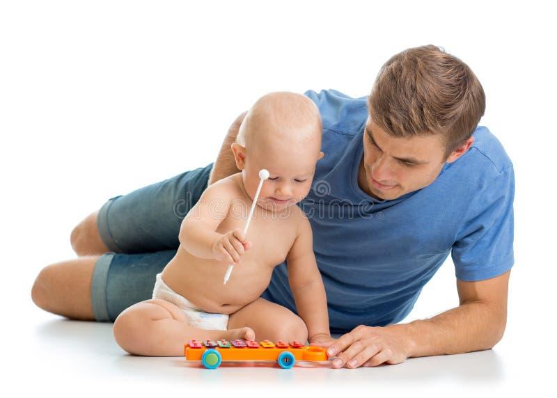El padre y el bebé se divierten con los juguetes musicales Aislado en wh imagenes de archivo