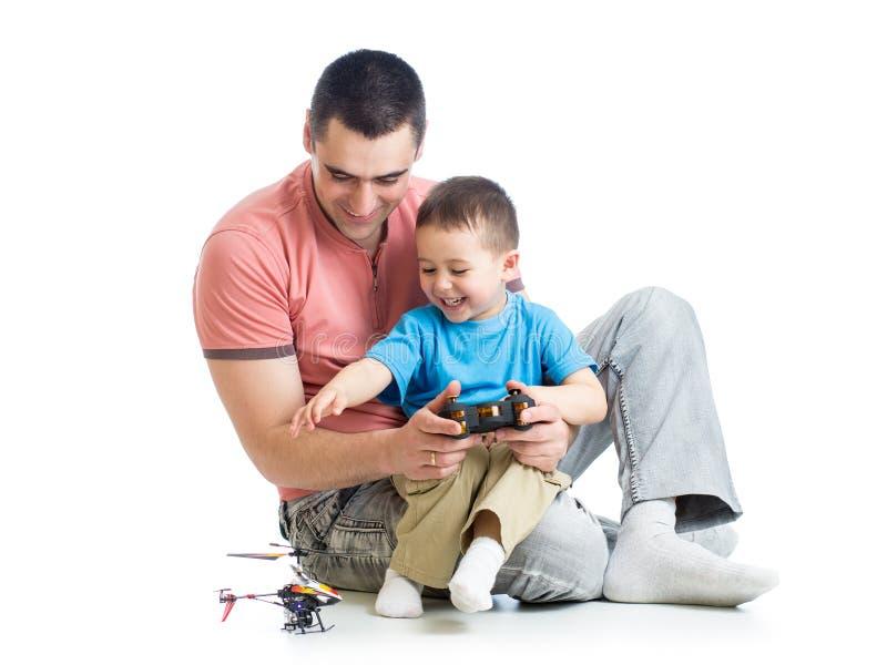 El padre y el hijo embroman jugar al juego del helicóptero de los niños foto de archivo