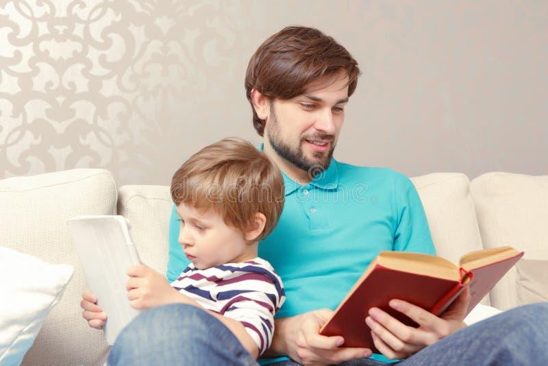 El padre y el hijo leyeron un libro o una tableta fotografía de archivo