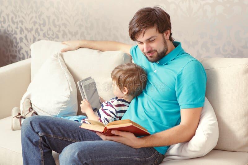 El padre y el hijo leyeron un libro o una tableta foto de archivo
