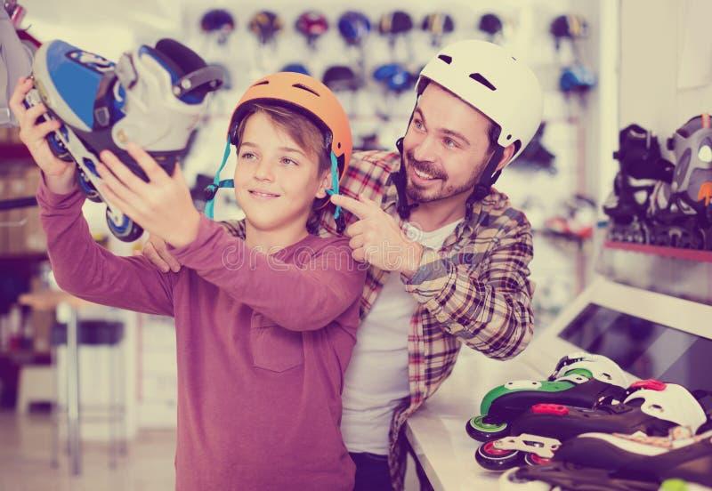 El padre y el hijo que deciden sobre nuevo patina sobre ruedas en tienda de los deportes imágenes de archivo libres de regalías