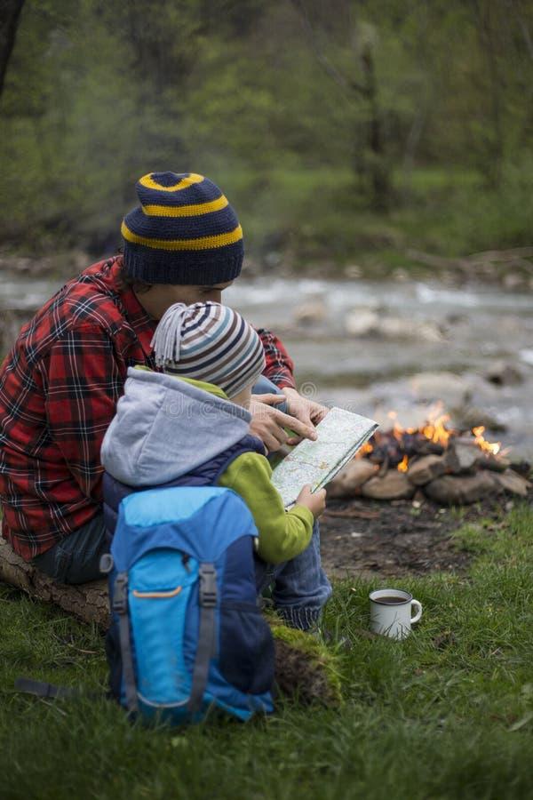 El padre y el hijo que se sientan cerca de una hoguera en el sitio para acampar y son l imagen de archivo libre de regalías