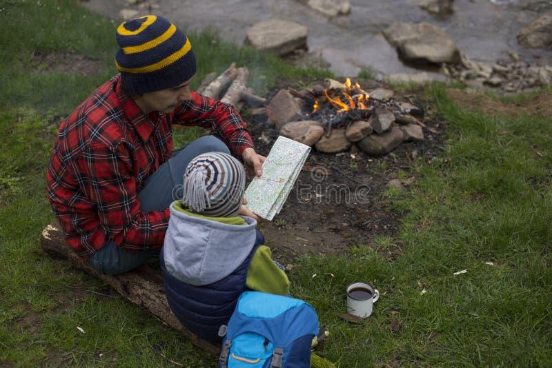 El padre y el hijo que se sientan cerca de una hoguera en el sitio para acampar y son l imagen de archivo