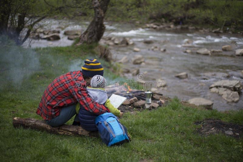 El padre y el hijo que se sientan cerca de una hoguera en el sitio para acampar y son l imágenes de archivo libres de regalías