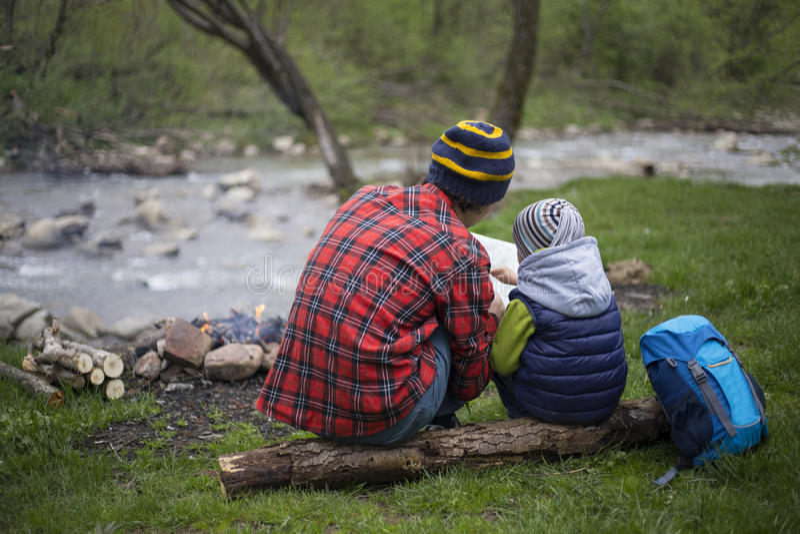 El padre y el hijo que se sientan cerca de una hoguera en el sitio para acampar y son l foto de archivo libre de regalías