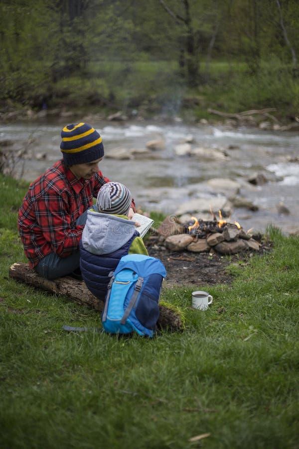 El padre y el hijo que se sientan cerca de una hoguera en el sitio para acampar y son l imagenes de archivo