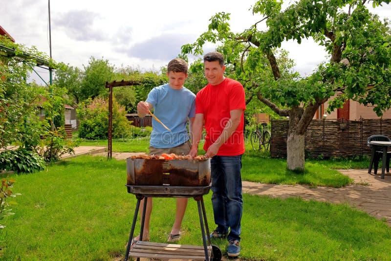 El padre y el hijo blancos atractivos son sonrientes y de asados a la parilla de kebabs foto de archivo