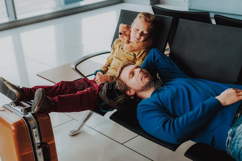 El padre y el hijo están durmiendo en salón del aeropuerto imagenes de archivo