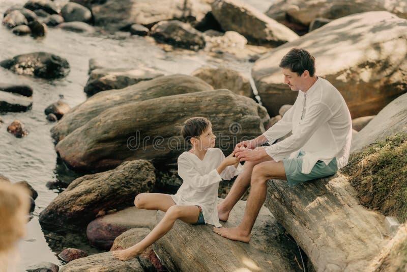 El padre y el hijo están jugando en rocas fotos de archivo libres de regalías