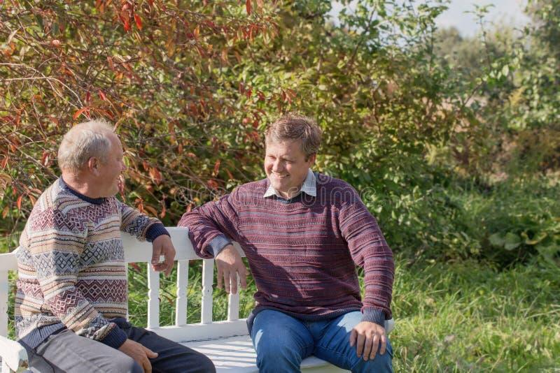El padre y el hijo mayores en banco en otoño parquean imagen de archivo libre de regalías