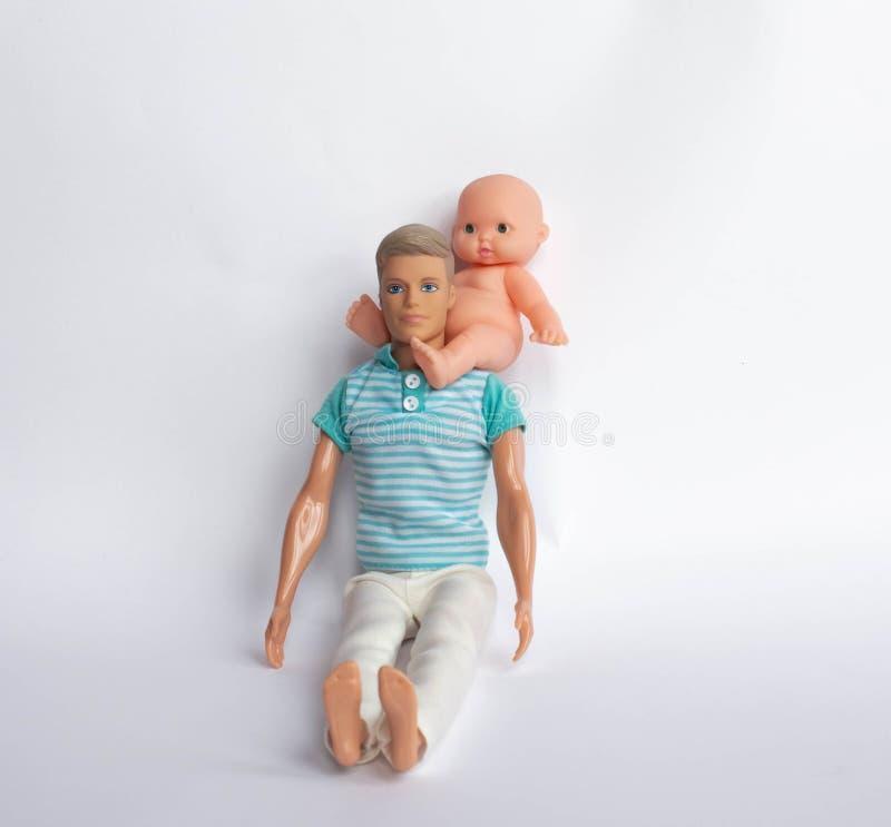 El padre y el hijo, muñecas en un fondo blanco, padre detiene al hijo en sus brazos, alimenta a su hijo El cuidar para la familia imagen de archivo