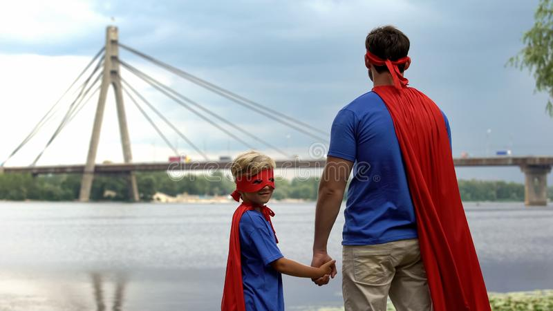 El padre y el hijo que llevan al super héroe divertido viste la mirada lejos, padre de apoyo imagenes de archivo