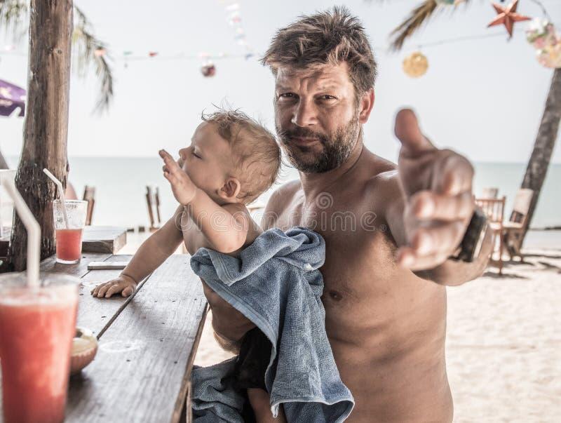 el padre y el hijo que se sientan en la playa barran al revés y requieren las bebidas imagen de archivo