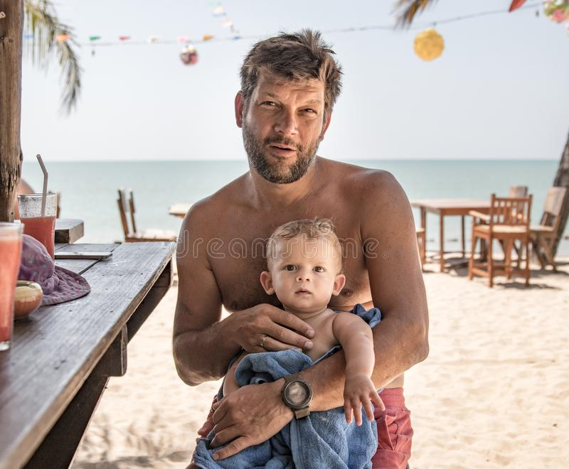 el padre y el hijo que se sientan en la playa barran al revés y requieren las bebidas fotografía de archivo libre de regalías