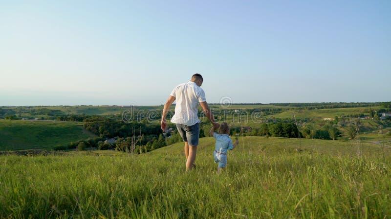 El padre y la hija comparten el amor que lleva a cabo las manos que caminan juntos en alto campo de hierba imágenes de archivo libres de regalías