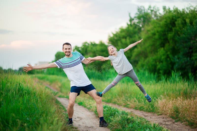 El padre y la hija hacen ejercicios acrobáticos imágenes de archivo libres de regalías