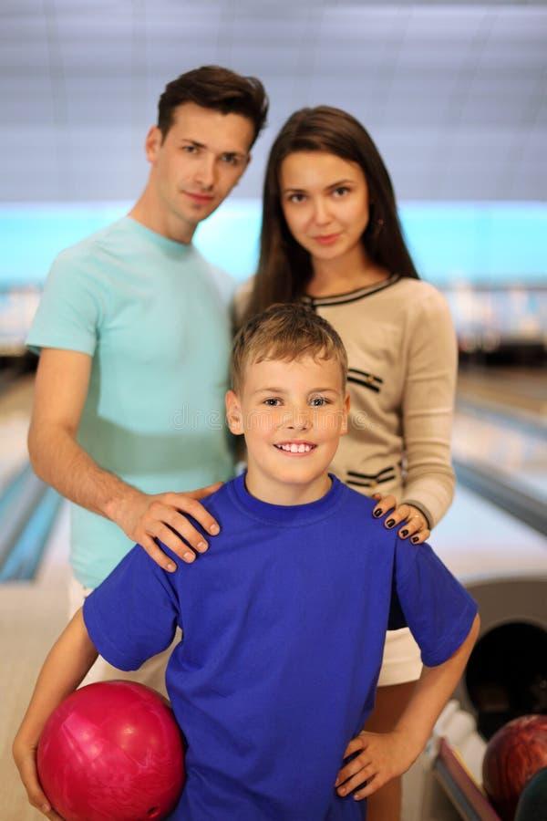 El padre y la madre con el hijo en el bowling aporrean imagenes de archivo