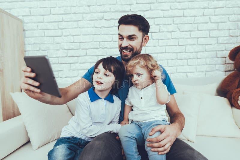 El padre y los hijos está mirando un vídeo en Tablet PC fotos de archivo