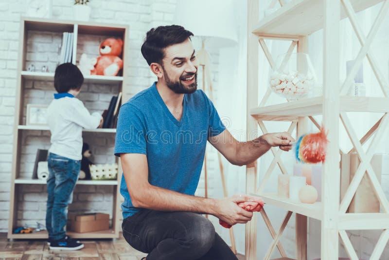 El padre y los hijos limpian superficies de los muebles del polvo fotos de archivo