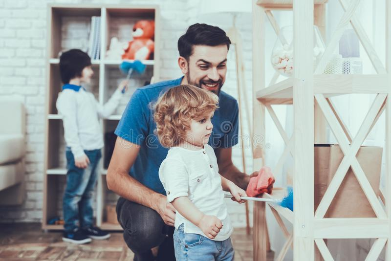 El padre y los hijos limpian superficies de los muebles del polvo imagen de archivo