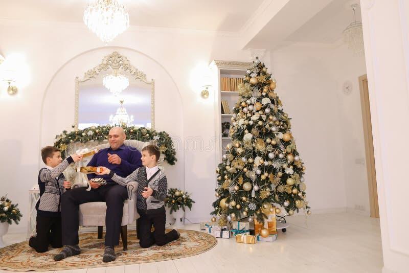 El padre y los niños con los muchachos gemelos intercambian los regalos y risa en l fotografía de archivo