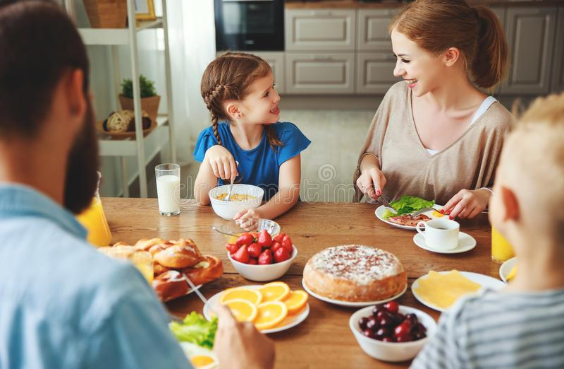 El padre y los niños de la madre de la familia desayunan en cocina por mañana imagenes de archivo