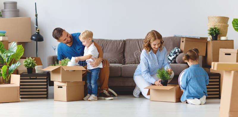 El padre y los niños felices de la madre de la familia se trasladan al nuevo apartamento foto de archivo libre de regalías