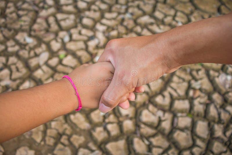 El padre y los niños llevan a cabo las manos para ayudarse a través fotos de archivo libres de regalías