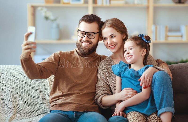 El padre y el niño felices alegres de la madre de la familia toman selfies, toman imágenes imagen de archivo libre de regalías