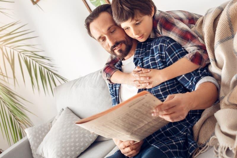 El padre y poco muchacho del hijo en casa que abrazaban al papá que se sentaba en el periódico de la lectura del sofá juntos se r fotos de archivo