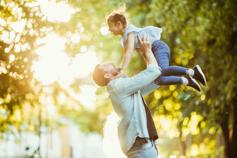 El padre y su hija son que juegan y de abrazos al aire libre en parque del verano en puesta del sol imagen de archivo