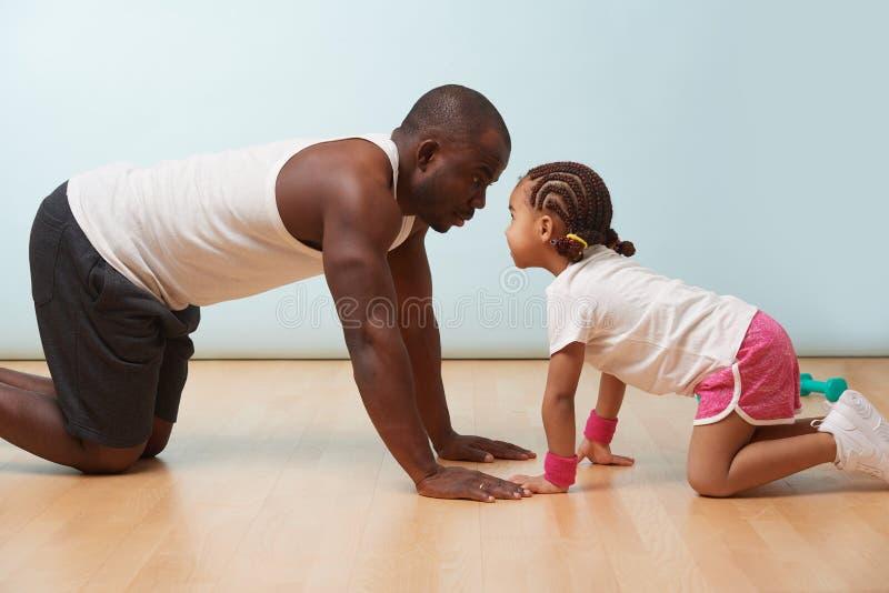 El padre y su pequeña hija están estirando juntos en el piso en casa fotos de archivo libres de regalías