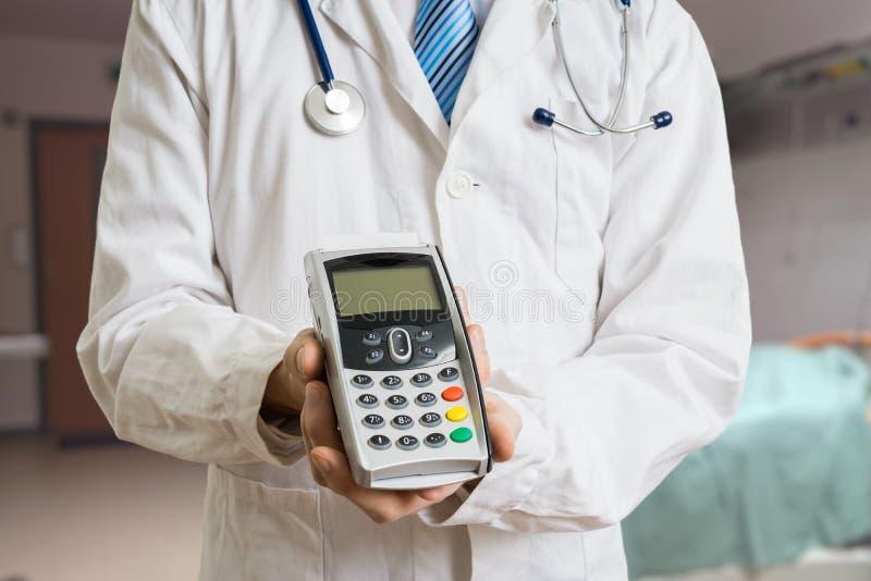 El pagar atención sanitaria privada El doctor lleva a cabo el pago terminal en manos imágenes de archivo libres de regalías