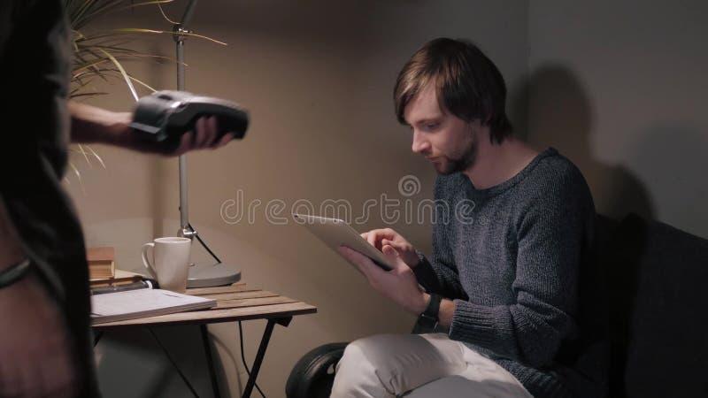 El pagar con smartphone Hombre hermoso que hace transacción del pago su teléfono móvil al camarero en café o tableta moderno imágenes de archivo libres de regalías