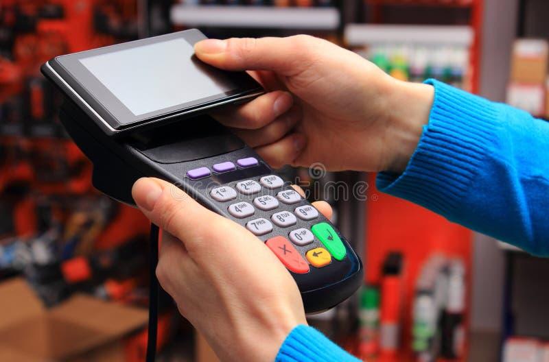 El pagar con tecnología de NFC en el teléfono móvil fotografía de archivo