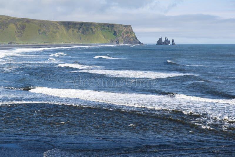 El paisaje atlántico de la costa del punto de opinión de Dyrholaey, de ondas y de Reynisdrangar oscila, Islandia del sur foto de archivo