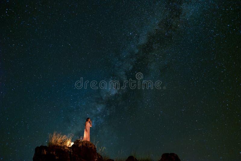 El paisaje con las mujeres mira para arriba a la vía láctea y protagoniza en la noche en c imagen de archivo libre de regalías