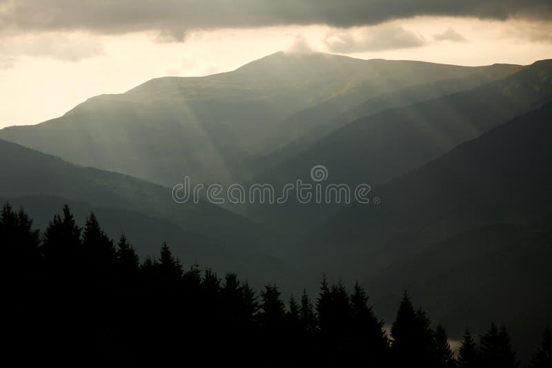 El paisaje de la montaña, el sol irradia a través de las nubes foto de archivo libre de regalías