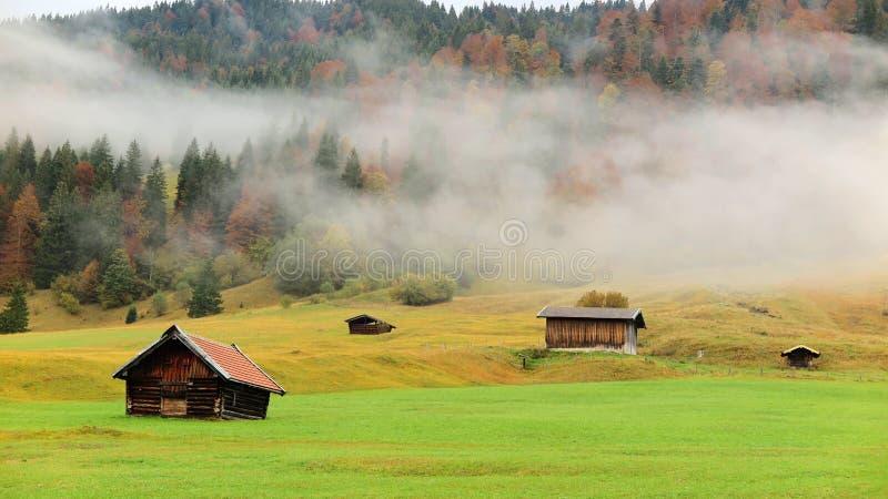 El paisaje del otoño del campo bávaro con el campo de hierba y los graneros de madera por mañana se empañan fotografía de archivo