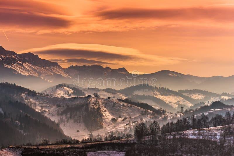 El paisaje hermoso del invierno en las montañas con las nubes lenticulares y la nieve en la puesta del sol se encienden imagen de archivo libre de regalías