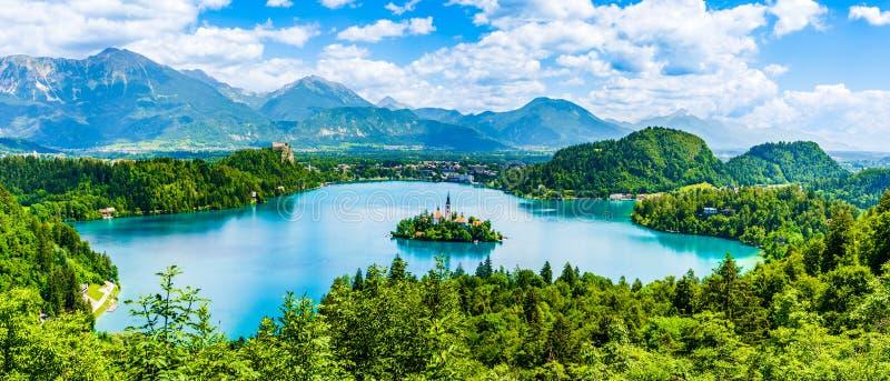 El paisaje hermoso del lago sangró la isla de la iglesia en el centro y el castillo en el fondo del cielo nublado blanco de imágenes de archivo libres de regalías