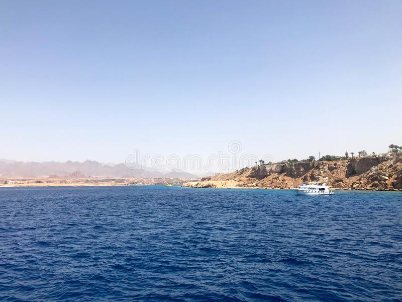 El paisaje marino de las montañas de piedra marrones tropicales hermosas distantes y los diversos edificios, la nave en la orilla foto de archivo libre de regalías