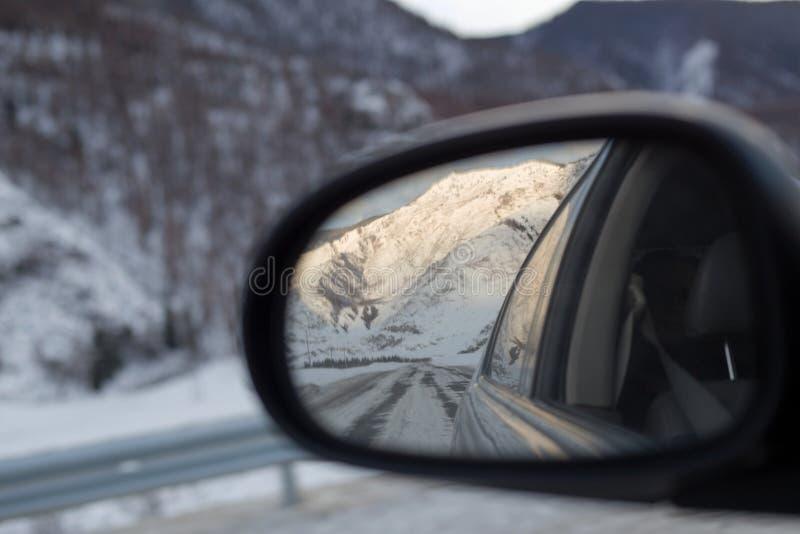 El paisaje nevoso de las montañas reflejó en el espejo de la vista posterior del coche foto de archivo libre de regalías