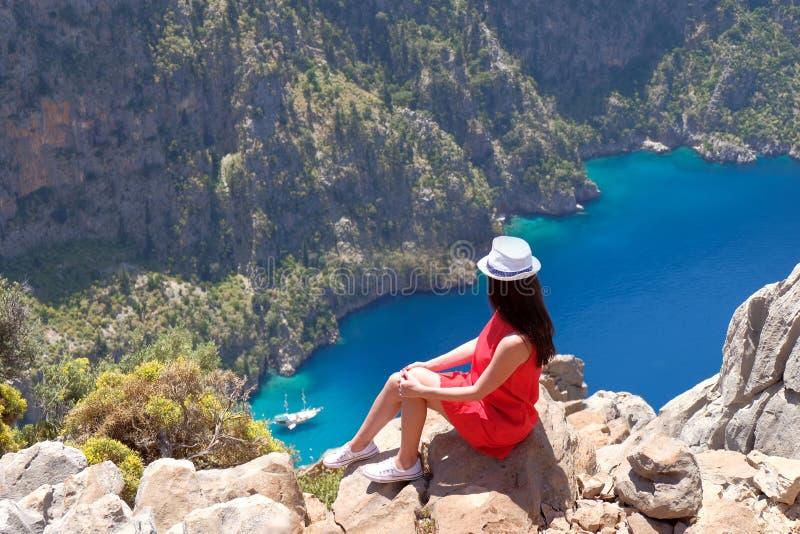 El paisaje Oludeniz, Turqu?a, una chica joven en un vestido rojo mira el Butterfly Valley desde arriba, sent?ndose en las rocas imagenes de archivo